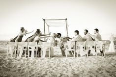 Photo of a bride and groom kissing each other while sitting on the beach, with the bridesmaids and groomsmen looking on. This photo was taken by Stop Motion Productions, a Bahamas Wedding Photographer.