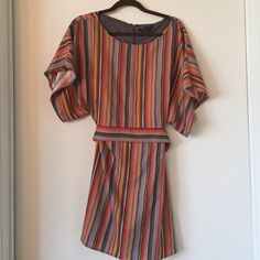 BCBG Max Azria Party Dress This vertically striped dress with a bow in the back is incredibly flattering! The colors are reds, purple, and yellows set against a tan background. The flowy sleeves add an element of whimsy. BCBGMaxAzria Dresses