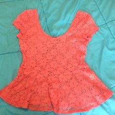 ✨Coral Peplum Top✨ Lace Peplum top with wide shoulders. Says large but could fit a medium as well. Has a tiny black spot but it's barely noticeable (pictured) Tops Blouses