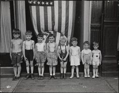 View of children of graded heights in front of the American flag, Victory celebrations, John Albok