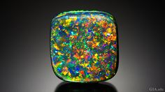 The play-of-color of this black opal cabochon shows flashes of green, blue, yellow, orange and red, in an attractive, even pattern.