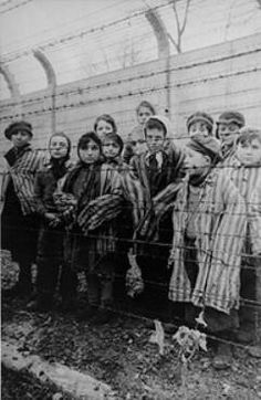 STILL FROM A POSTWAR SOVIET FILM:  Jewish children, kept alive in the Auschwitz II (Birkenau) concentration camp, pose in concentration camp uniforms between two rows of barbed wire fencing after liberation.  (After January 27, 1945)