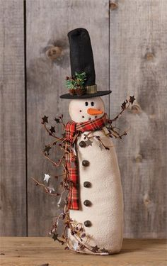 3ce4674db83d3 This is a new snowman doll that has a garland of rusty stars and berries.