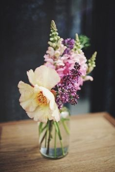 Snapdragons and lilac in a glass bottle