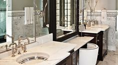 Glam bathroom with half gray walls and marble tiled lower walls and backsplash with mosaic inset tiles, featuring a drop-down vanity flanked by espresso inset cabinets all with calcutta marble countertops. Rustic Bathroom Wall Decor, Gray Bathroom Walls, Brown Bathroom, Bathroom Floor Tiles, Bathroom Cabinets, Grey Walls, Tiny Bathrooms, Guest Bathrooms, Glamorous Bathroom
