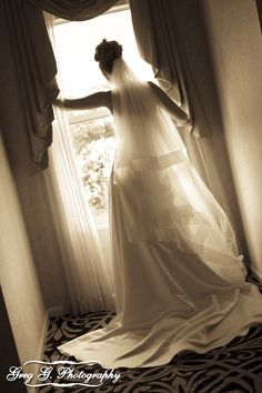 Bride standing by window, looking out on her groom helping to get things ready outside.
