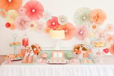Pastel pinwheel and pom pom backdrop to this beautiful dessert table