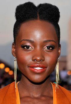 Lupita Nyong'o usa look monocromático com o batom laranja seguindo a mesma nuance da sombra e blush.