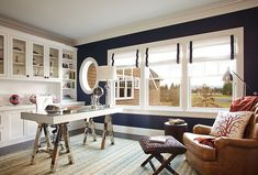 A prime example of a highlight wall in thick navy with the rest of the room in crisp white. Note the wood flooring. I like the nautical touch on the Roman blinds, too. Excellent for the windows by the bookcases and the patio door.