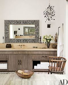 Cabinet finish. Elegant surfaces predominate in the master bath, with stained-walnut vanities, limestone countertops, and a marble floor; the mirrors with mother-of-pearl inlay are from India, the mobile is by Kevin Inkawhich, and the bronze cat sculpture is by Diego Giacometti.