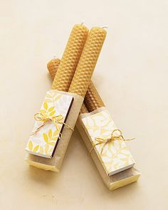 Bees wax candles with matchboxes covered in decorative papers. and tied with preety yarn or metallic gold cording