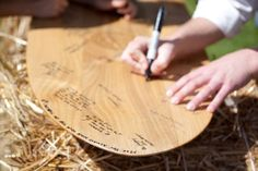"""hay bales used as tables and seats for wedding receptions   couple bales of hay with the sign """"love notes"""" in front."""