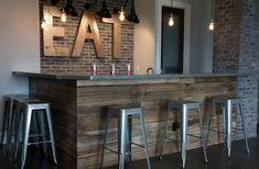 Rustic basement bar crafted from reclaimed wood and brick >> knee wall idea for kitchen bar