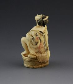 JAPANESE CARVED IVORY NETSUKE BATHING GEISHA Japanese carved ivory netsuke featuring seated Geisha in floral robe, open in front. Bottom features signature. Weight: 18.5 g Size: 2""
