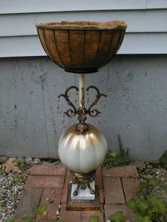 Plant stand using an old lamp, with a hanging basket attached to the top.