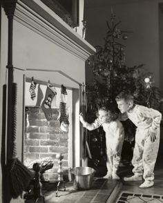 Boy and his sister peeking into a fireplace