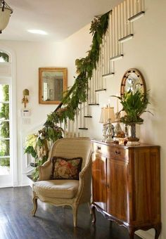 50 Stunning Christmas Staircase Decorating Ideas - Style Estate - A sunny entryway with simple seasonal decor. Artichokes and a silver bow are fun trimming on a garland of greenery. Christmas Staircase, Christmas Home, Christmas Decor, Southern Christmas, Christmas Greenery, Simple Christmas, Xmas, Traditional Decor, Traditional House