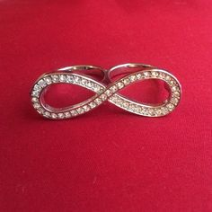 Double Finger Infinity Ring Gorgeous two finger silver infinity ring. Never worn, no scratches or stones missing. It was given to me as a gift so I am not sure what size the rings are, but most likely size 8.5 or 9. Both rings are the same size. Beautiful eye-catching  ring! Jewelry Rings