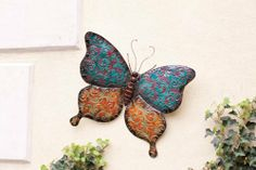 """31"""" Multi-Colored Metal Butterfly with Scroll Pattern Home Wall Decor by Cape Craftsmen. $64.99. Multi-Colored Metal Butterfly with Scroll Pattern Item #6M130This butterfly features a colorful, intricate scroll pattern on it's wingsFor indoor useDimensions: 30.5""""H x 31""""W x 6.25""""DMaterial(s): metal. Save 13%!"""