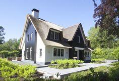 Witte rietgedekte villa met natuursteen trasraam, houten accenten en schoorsteen te Blaricum - 01 Architecten - ontworpen door Dennis Kemper tijdens de periode dat hij bij EVE-architecten werkte.