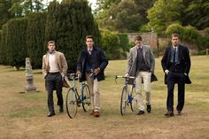 walk across a private garden in formalwear, two with bikes, two without.