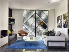 Small and stylish living area in white and black with rug adding a dash of blue