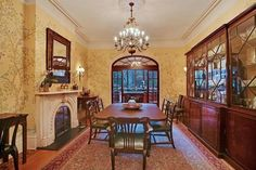 This Lenox Hill Townhouse has a patterned area rug, dark wood built in display cabinets, arched openings, ornate fireplace, crown molding and yellow chinoiserie wallpaper.