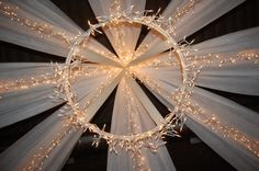 Canopy made from hula hoop, white landscaping fabric and icicle lights, used at wedding reception.