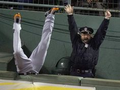 Boston police officer Steve Horgan celebrates as Detroit Tigers rightfielder Torii Hunter falls over the fence into the bullpen trying to catch a homerun ball
