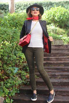 Pantalones en verde y zapatillas en blanco y negro y jersey también y chaqueta negra estilo clásico y bolso en rojo y dorado y bandana en rojo y gorro en negro y gafas en negro