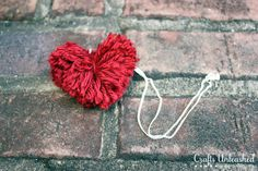 Learn how to make a yarn pom pom Valentine heart necklace with this easy to follow tutorial. They are so easy to make so so cute!