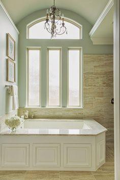Framed deep soaking tub, soft colors and tile.