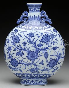 """19th century, China. Moon shaped with archaic dragon handles. Underglaze blue decoration of stylized lotus flowers with jui-i, acanthus and thunder meander borders. 19"""" h"""