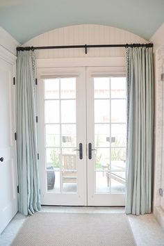 rounded ceiling with neutral curtains by doors