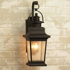 """Classical Refinement Outdoor Wall Lantern This classic outdoor wall lantern will add sophisticated curb appeal. With its faux vented top and a sloping roof, the squared frame is finished in a textured matte Black with seeded glass panels for diffused light. 100 watts. (medium base socket) (23""""Hx8""""Wx10.5""""D)"""