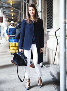 A navy coat is paired with white pants, snakeskin heels, and a navy purse