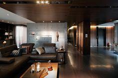 salon contemporain sombre aménagé avec un canapé en cuir marron, un mur de séparation en béton banché et un faux plafond en bois sombre