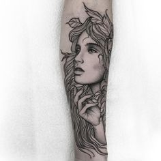 Tatuagem criada por Thomas Bates da Inglaterra. Rosto feminino com flores no cabelo em blackwork.
