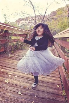 Photo of a little girl twirling by Olive Belle Photography