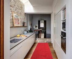Deko in Rot mit einem Läufer in einer modernen, weißen Küche