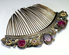 French Second Empire comb, mid-19th century, Width : 4 7/8 inch, Height : 6 7/8 inch, Depth : 1/8 inch, Gorgeous Empire style comb with floral decoration. Colored glass cabochons evoking amethyst and rubies.