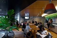 This image shows a Bank's new workspace. It is  conceived as sustainable and flexible. The image shows persons working under adequate lighting; transparency, openness and connectivity to meet clients' needs.The image shows a more people friendly workspace which will allow staff to relax and recharge.