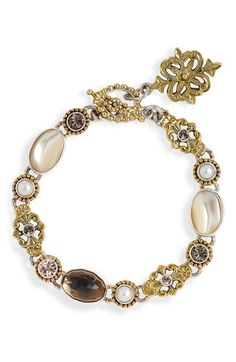 Fine filigree ices a sumptuous handmade bracelet of creamy pearls and sparkling stones.
