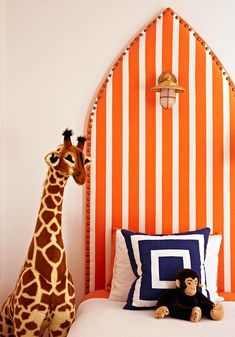 Fun blue and orange boy's bedroom with white and orange striped headboard with brass nailhead trim and antique brass marine sconces installed on headboard.