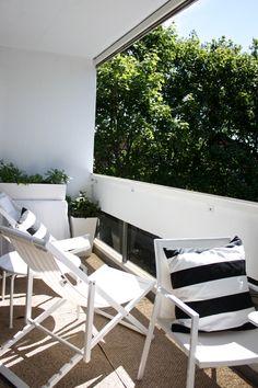 homevialaura | summer | city balcony | white outdoor furniture | Pappelina Svea rug in Nougat | striped cushion