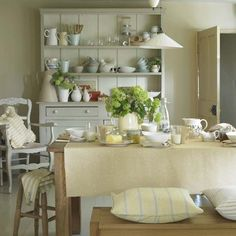 Soft, warm colours and dairy accessories help to create this cosy, family kitchen. Carvers, benches and stools have been used for farmhouse-style seating. The look is completed with mix and match crockery for an eclectic look.
