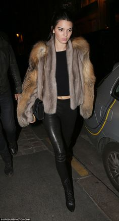 Super chic:Kendall kept warm in the chilly Paris temperatures in her furry coat, which she layered over a fitted black crop top which flashed a hint of her toned stomach