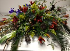 "Masculine casket spray for an outdoors man. Rust lilys, blue iris, solidago and blue thistle accomponied by lotus pods, Natraj, seeded Euclyptus, tree fern, plumosia fern, pheasant feather and palm fronds — at Auburn ""Classic"" Florist."