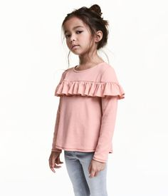 Dusky pink. Long-sleeved top in soft jersey with a shoulder-level ruffle, decorative stitching in glittery thread, and gently rounded hem. Slightly longer