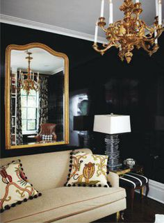 High gloss black walls, bold colors, floor to ceiling books, oversized light fixtures, brass accents
